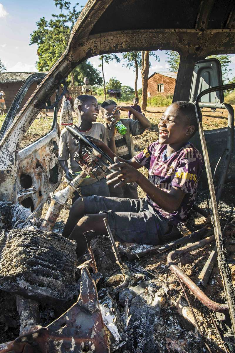 Kids playing in a burned out minibus, Malawi