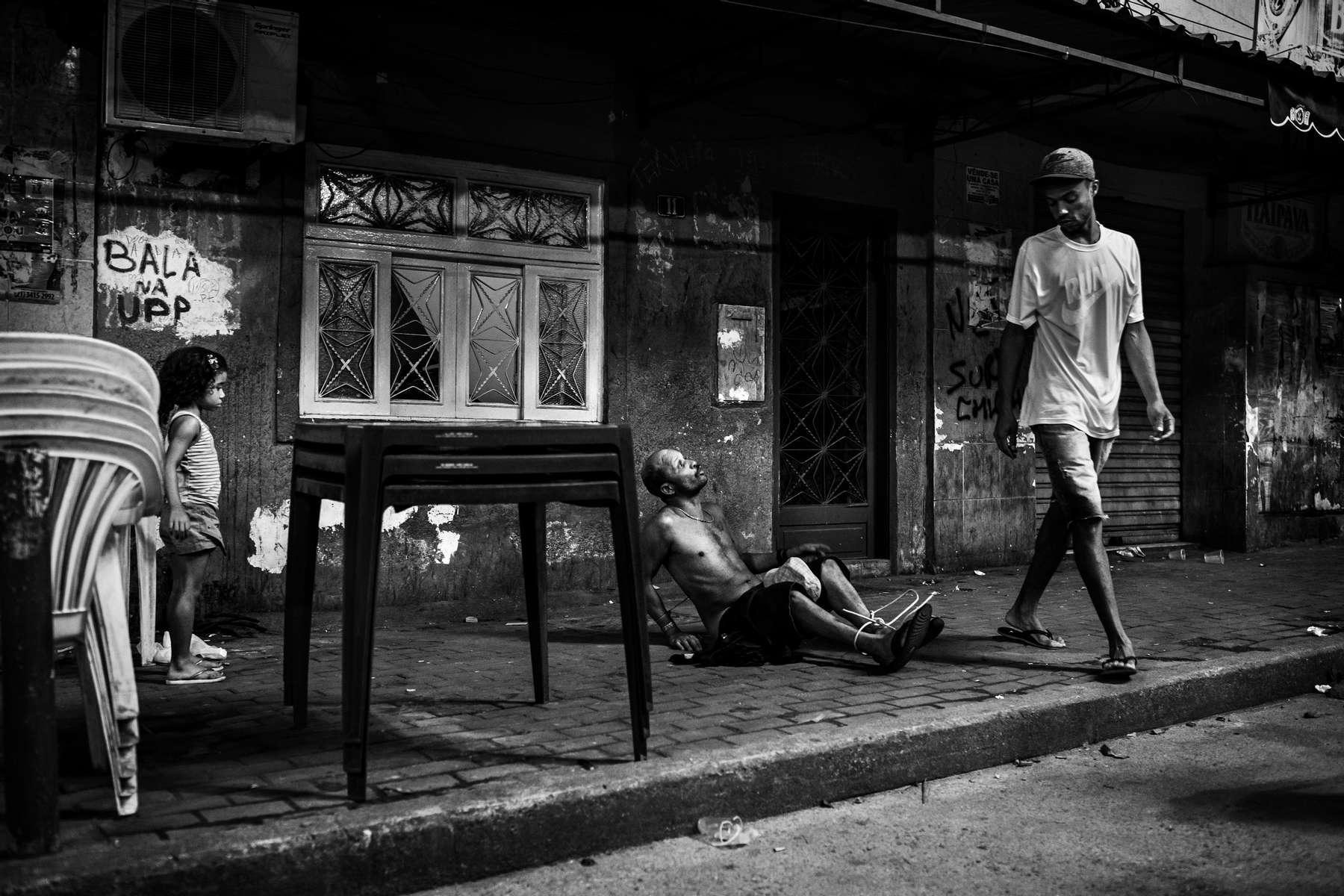 Un adolescente se aleja después de atar a un hombre borracho ante una niña en el barrio marginal de Rocinha durante un partido de fútbol antes de la Copa Mundial 2014, el 11 de mayo de 2014, en Río de Janeiro, Brasil.Durante la transmisión del juego en una plaza pública, dos hombres decidieron amarrar a un tercero después de que molestara repetidamente al resto de los fanáticos que estaban viendo el partido.