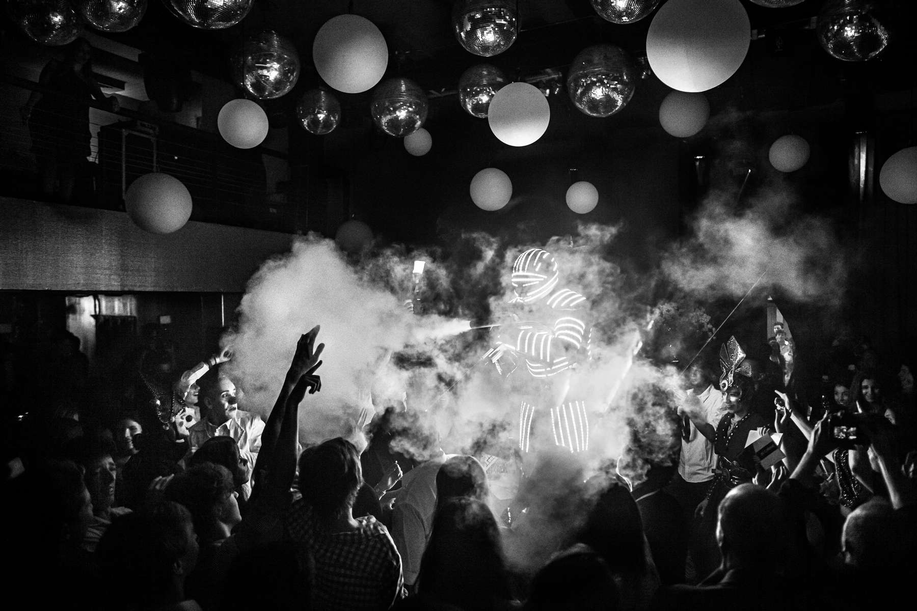 Un 'LED-Robot' dispara dióxido de carbono mientras se dirige a la pista de baile de una fiesta temática del {quote}Cirque du Soleil{quote}, en Río de Janeiro, Brasil, el 9 de noviembre de 2013.La fiesta de las Quinceañeras es la celebración del decimoquinto cumpleaños de un adolescente, que se celebra de una manera completamente diferente a cualquier otro cumpleaños y representa la transición de una niña a una mujer adulta. Grandes cantidades de dinero se gastan anualmente en Brasil en estas celebraciones.