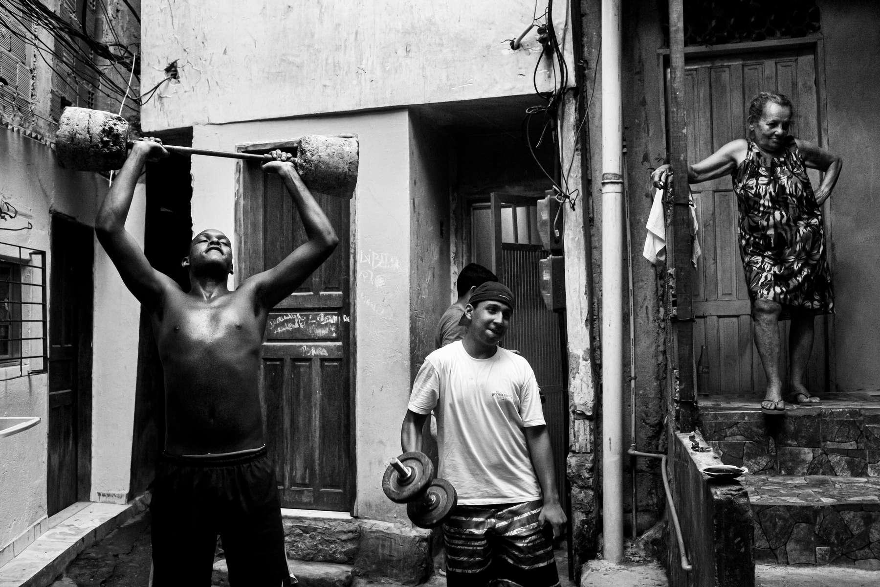 Un grupo de adolescentes entrena levantando pesas mientras una anciana los mira en el Barrio de Rocinha, la favela más grande de Río de Janeiro, Brasil, 18 de diciembre de 2012.