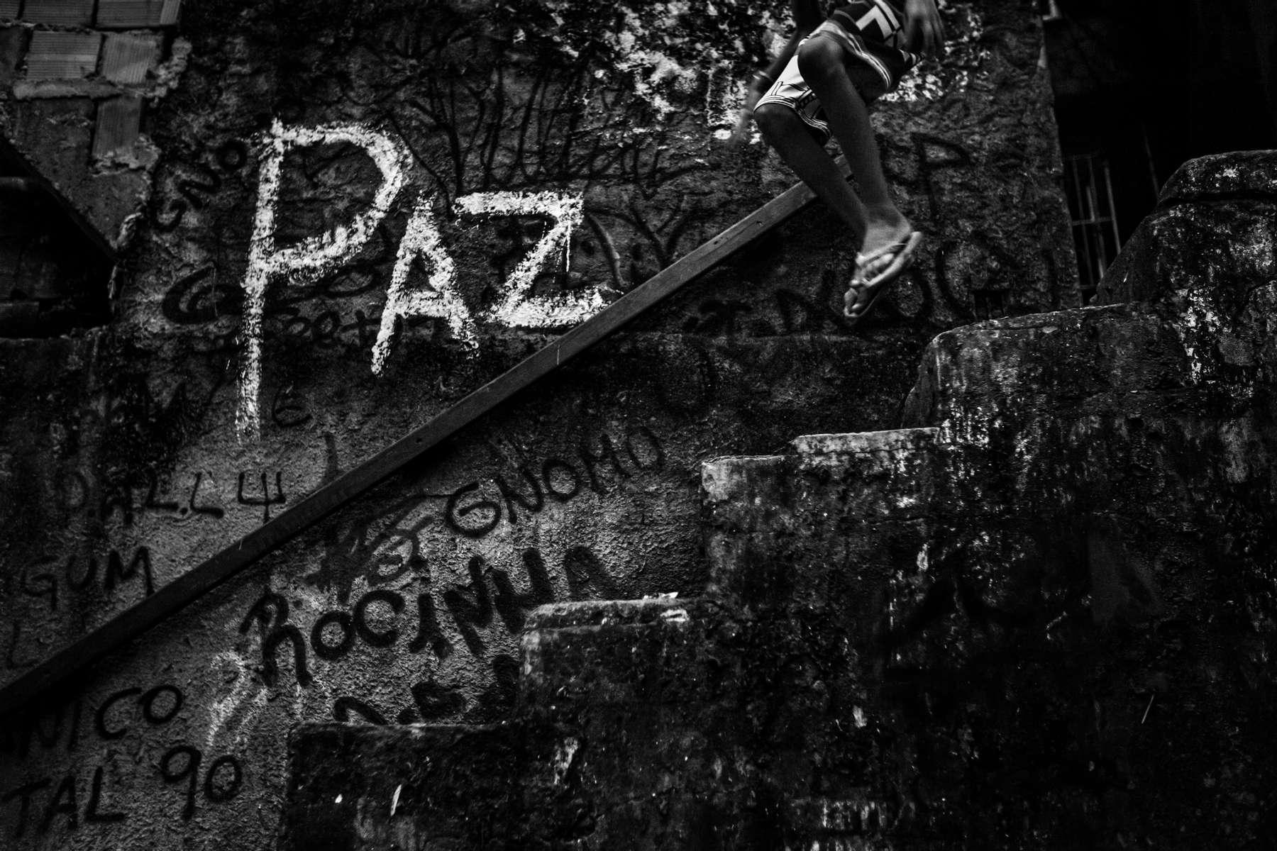 Un joven salta por una escalera con la palabra {quote}paz{quote} escrita en la pared, en la comunidad de Rocinha, la favela más grande de Río de Janeiro, Brasil, el 22 de febrero de 2012.
