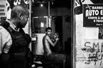 El soldado de la UPP. Franca, camina frente a una barbería mientras su dueño le corta el pelo a un cliente, en la favela de Sao Carlos, en Río de Janeiro, Brasil, el 15 de marzo de 2012.
