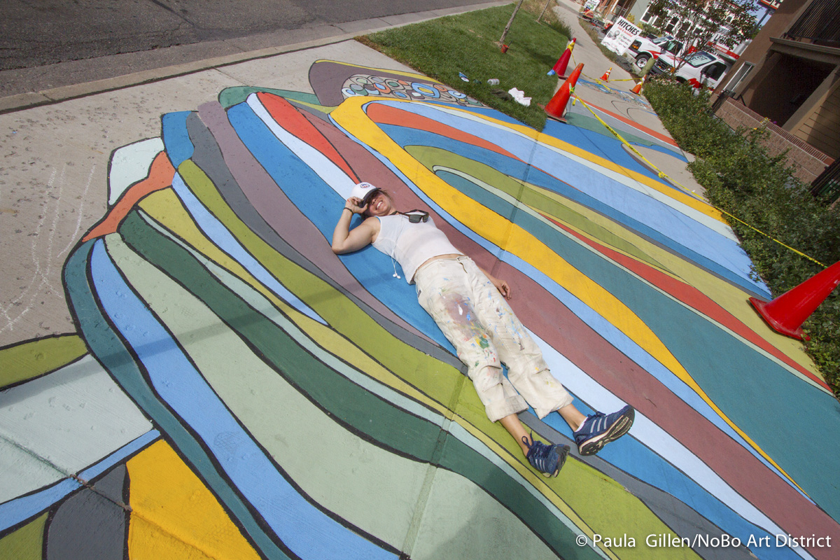 Artist Katherine Homes and her painted sidewalk mural on Broadway in north Boulder, CO. Sept. 2015.