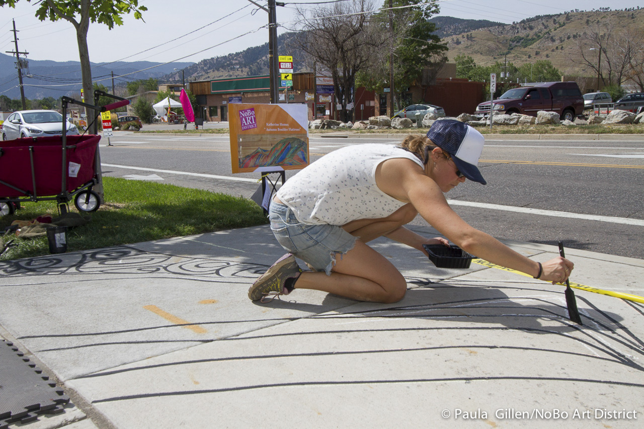 Artist Katherine Homes outlines her design on the sidewalk. Boulder, CO 2015