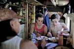 Michael, son fils Marshall et Hayden un jeune boxeur déjeunent dans le bus. Afin de pouvoir voyager facilement Michael a équipé son bus comme un petit appartement avec une cuisine, une douche et un lit. Katherine, TN, Australie, Juillet 2013.