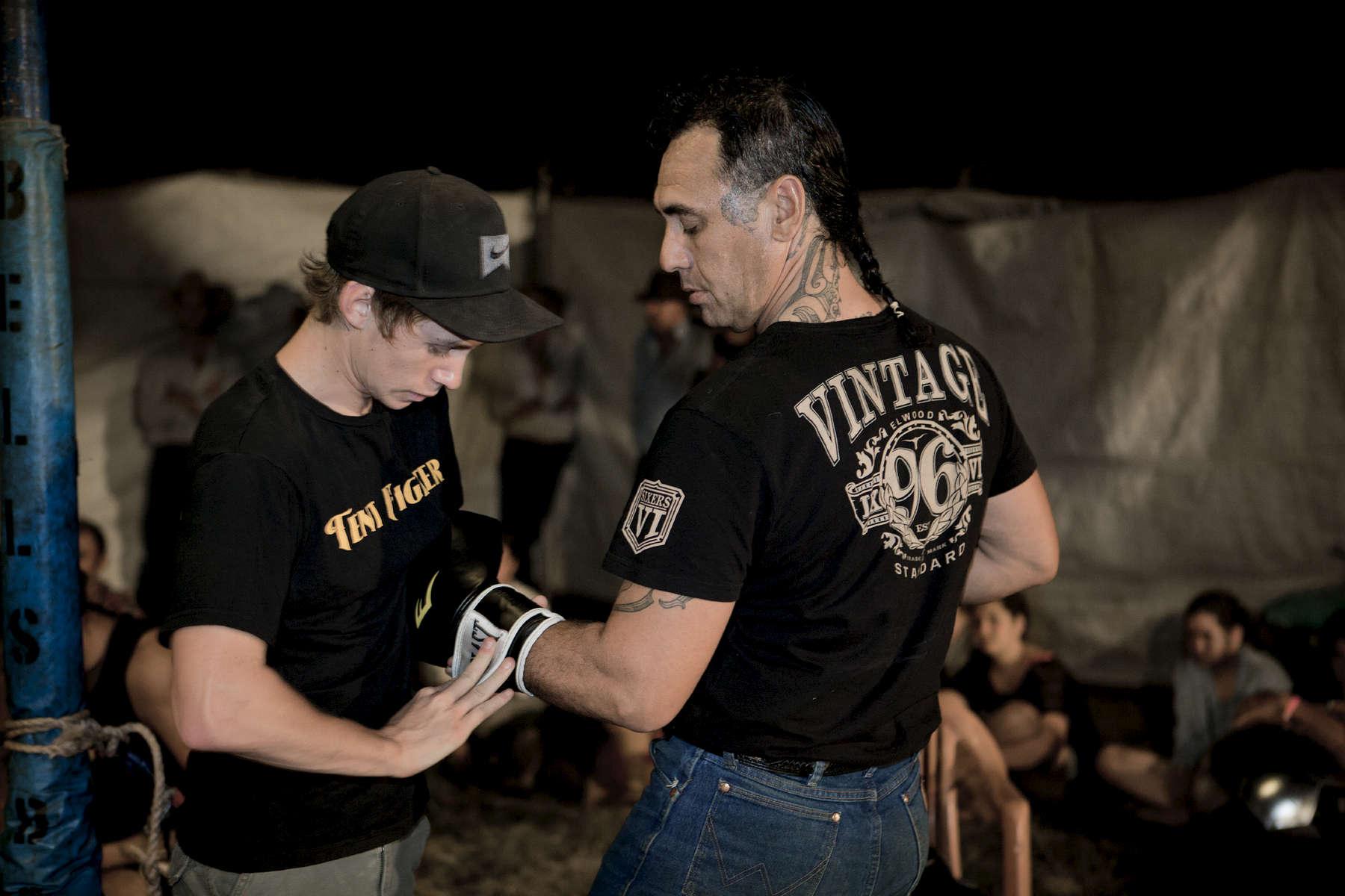 De temps en temps, Michael monte sur le ring. La foule apprécie toujours ce spectacle. Il a la réputation d'avoir été un très bon boxeur du temps où il pratiquait. Ici, son fils Marshall l'aide à mettre les gants. Katherine, TN, Australie, Juillet 2013.