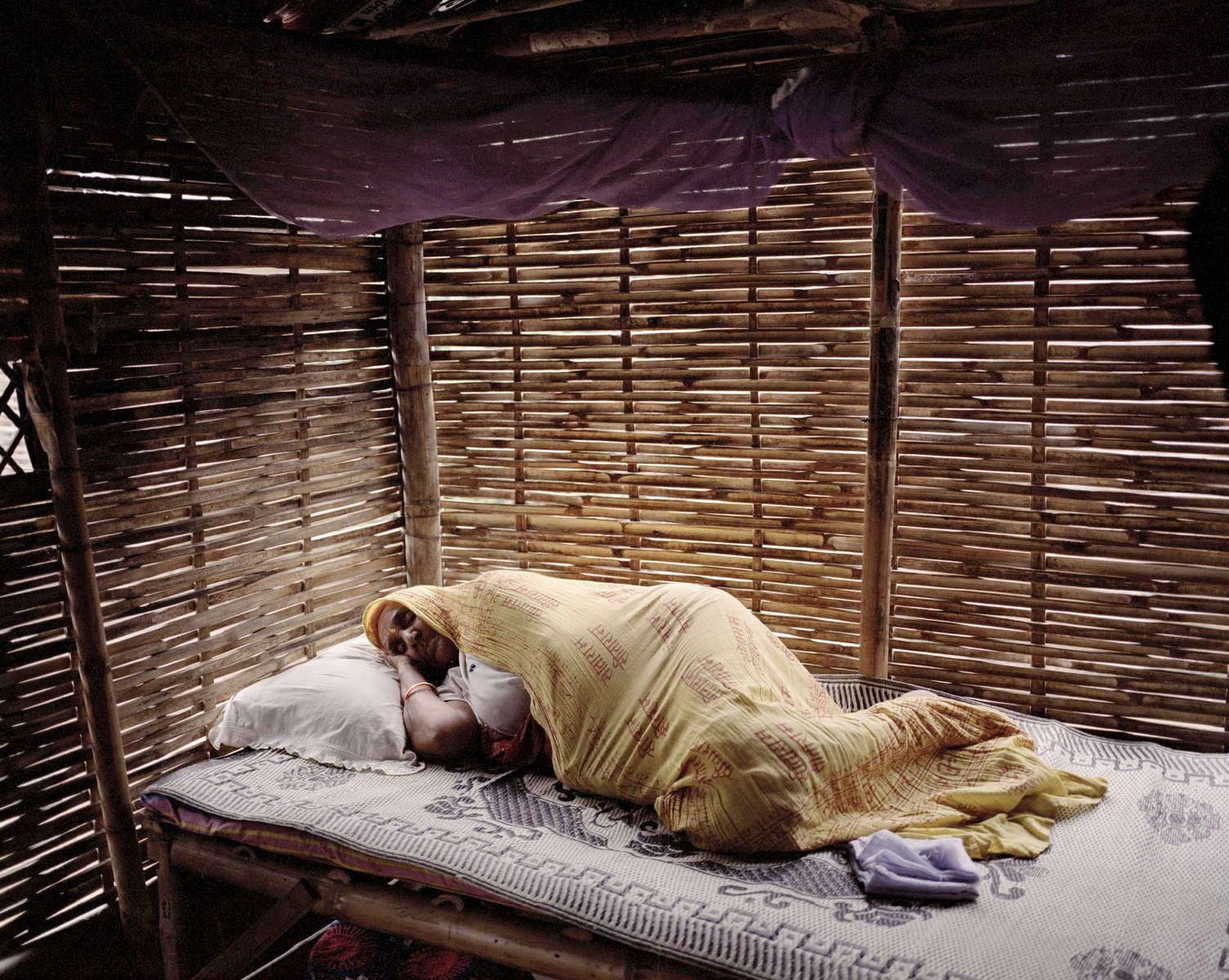 Radika Mainali se repose dans la hutte où elle vit avec son fils, sa belle fille et leurs deux filles. Népal, 2009.