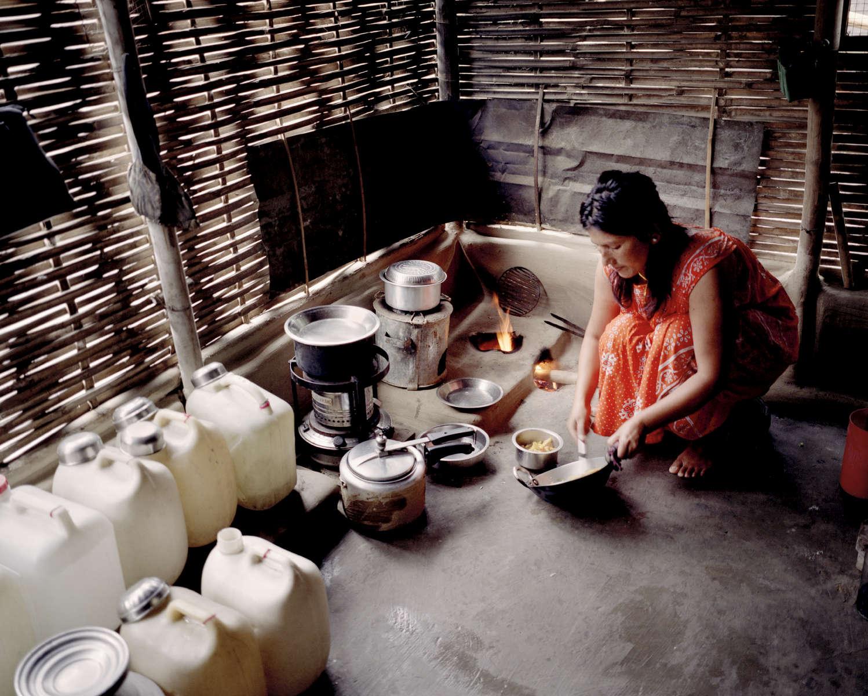 Hema cuisine dans la hutte pour sa famille. Népal, 2009.