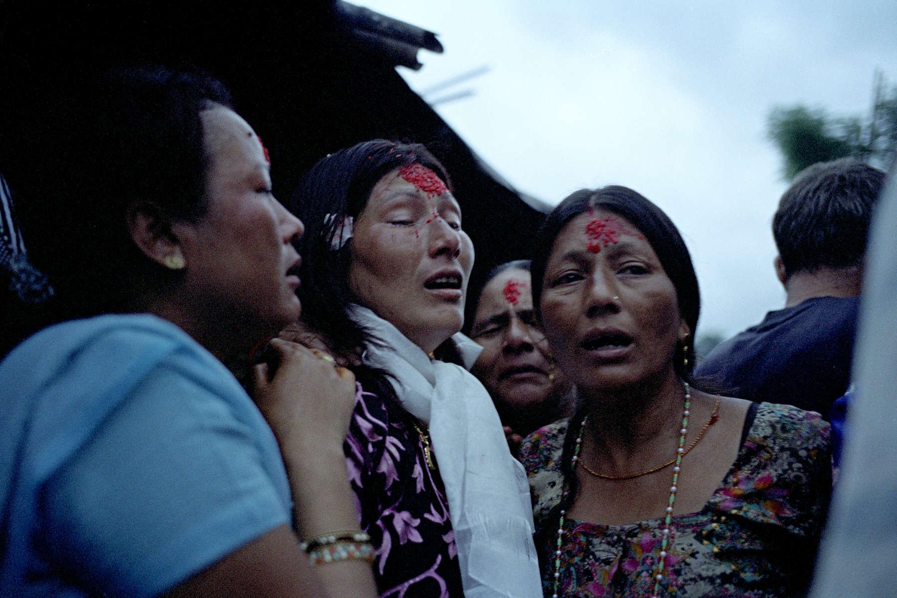 6 heure du matin, le jour du grand départ: les proches de la famille Mainali se rassemblent devant leur hutte pour leur souhaiter un bon voyage. Ici les femmes déposent sur le front de Hema la tika (rituel Hindou). Népal, Août 2009, Népal.