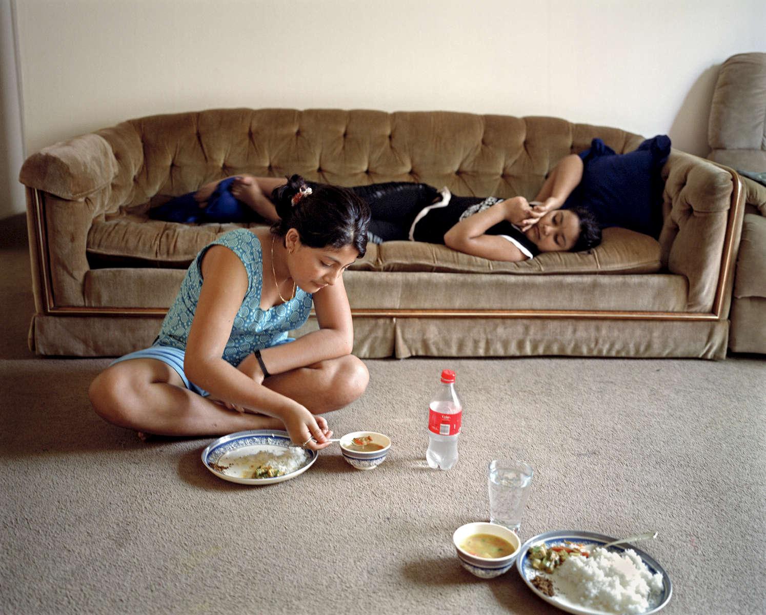Bidhya et Rabina, dans leur nouvel appartement en train de manger un dal bhat, plan traditionnel Népalais. Dallas, Texas, Etats-Unis, 2009.