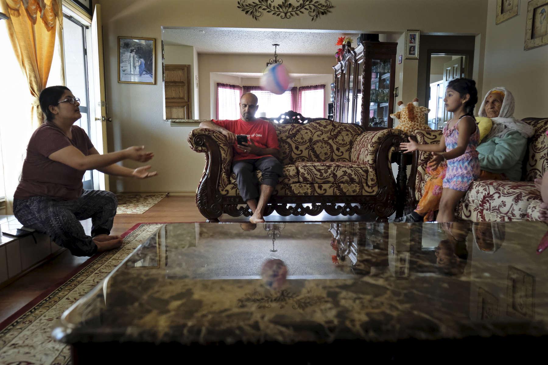 Aujourd'hui Rabi ne travaille pas, c'est rare. Il reste à la maison avec ses filles et sa mère. Watauga, Texas, Etats-Unis, 2018.
