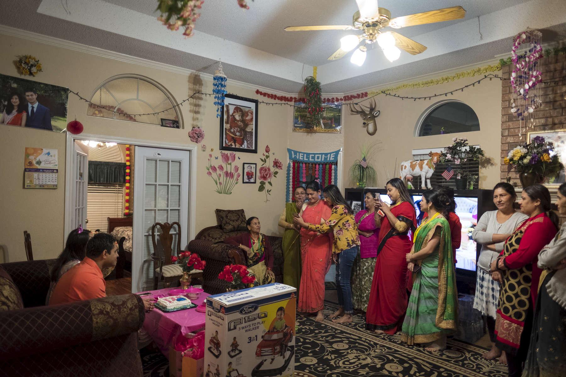 Pour célébrer l'arrivée imminente d'un nouvel enfant, la communauté Boutannaise du quartier se réunit et organise une babyshower. Ceci n'a rien à voir avec leur culture et leur tradition. Ils en organisent depuis leur arrivée aux Etats-Unis. Toutes les femmes qui assitantent à cette baby shower vivaient dans le camp de Beldangi au Népal tout comme la famille Mainali. Watauga, Etats-Unis, 2018.