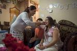 Hema offrant une cuillère de gateau aux futurs jeunes parents en guise de bonne chance et bonheur. Pour célébrer l'arrivée imminente d'un nouvel enfant, la communauté Boutannaise du quartier se réunit et organise une babyshower. Ceci n'a rien à voir avec leur culture et leur tradition. Ils en organisent depuis leur arrivée aux Etats-Unis. Toutes les femmes qui assitantent à cette baby shower vivaient dans le camp de Beldangi au Népal tout comme la famille Mainali. Watauga, Etats-Unis, 2018.