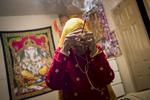 Radika priant dans sa chambre devant un autel représentant des divinités hindous. Les Lothsampas sont de confession Hindou. La communauté de Dallas a émi le souhait de lever des fonds pour la construction d'un temple, mais le projet reste encore en suspens. Watauga, Etats-Unis, 2018.