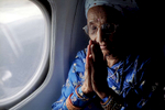 Radika s baptem. Radika mainali, in a plane for the first time in her life, praying before they take off. August 2009.