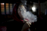 Farkhonda smoking chicha in Kabul, Afghanistan. November 2012.