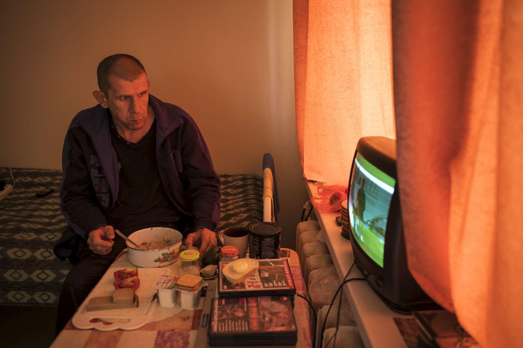 Dmitry, 48 ans est de Minsk. Dmitry est atteint de tuberculose multi-résistante. Il est un ancien prisonnier, il a passé 25 ans derrière les barreaux. Il a été libéré en 2012 de la prison de Orsha. En 1988-1989 il a eu une pleurésie et une pneumonie, ils ont pompé 5 litres de liquide hors de lui. C'est ainsi qu'ils ont détecté la Tb. Il est à l'institut depuis 7 mois. Comme la plupart es patients, Dmitry préfère prendre son repas seul dans sa chambre. Institut Républicain de la Tb, Minsk, Bielorussie, 2018.