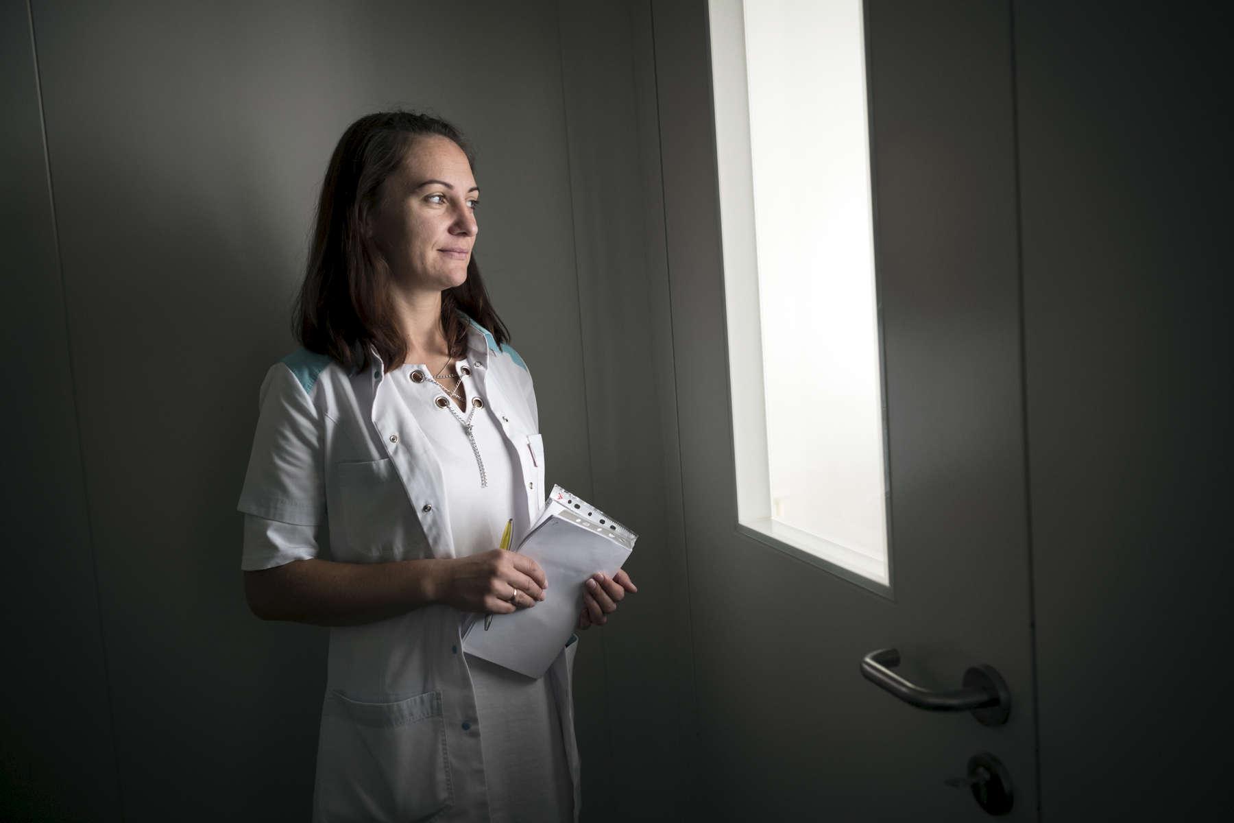 Alena, infirmière chez MSF regarde Leonid à travers la porte vitrée de sa chambre. Léonid n'est pas autorisé à sortir de cette chambre. Cela fait un mois qu'il y est. Unité intensive de soins. Institut Républicain de la TB, Minsk, Bielorussie, 2018