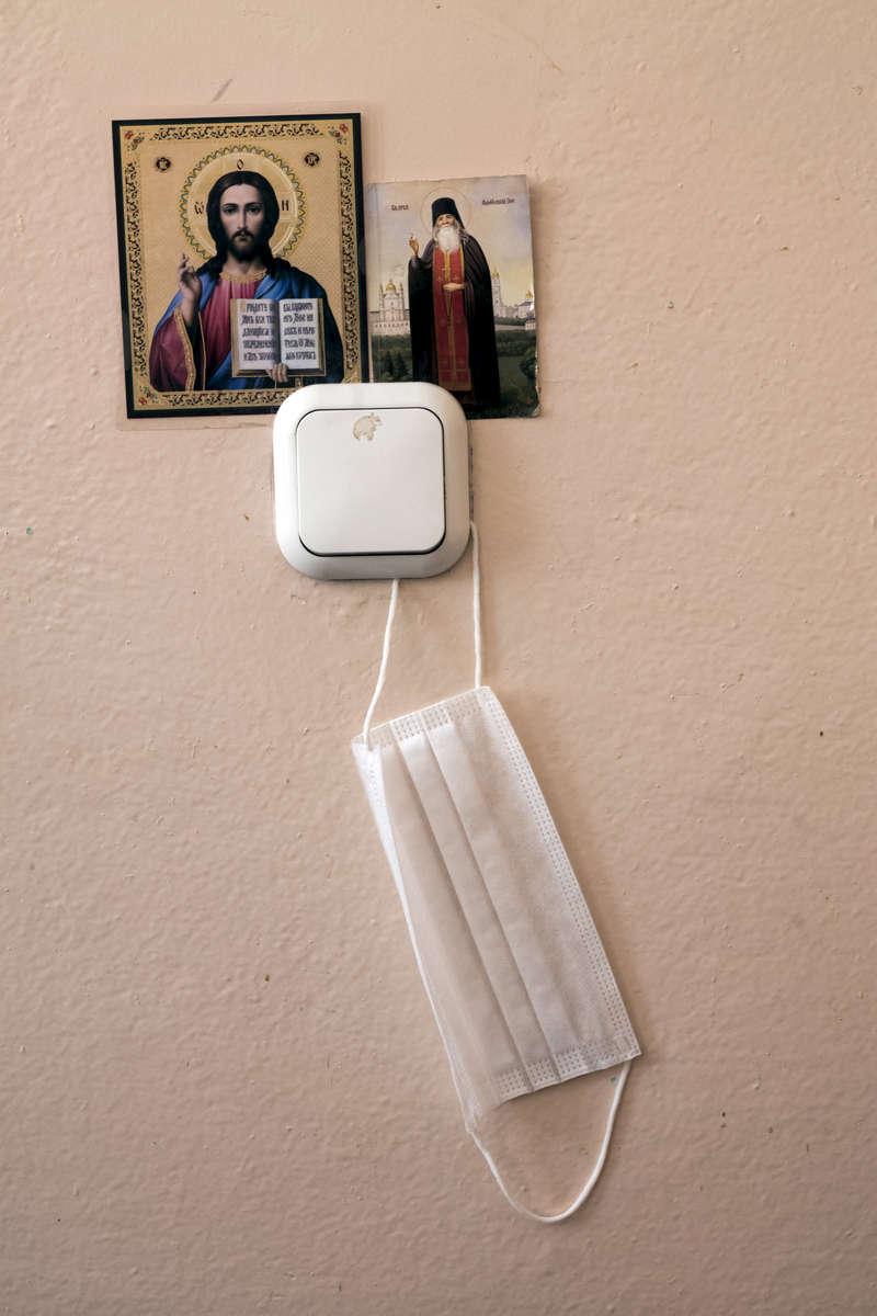 Masque et icônes religieuses accrochés au mur dans la chambre d'un patient. Institut Républicain de la TB, Minsk, Bielorussie, 2018