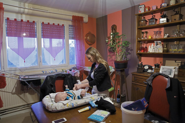 Laurine change son fils sur la table du salon chez son père. Au terme de sa grossesse, elle a arrêté l'école. Elle aimerait reprendre son C.A.P vente. Fourmies, France.