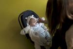 Thiméo regarde une photo que Laurine vient de prendre de lui avec son téléphone. Laurine est fière d'être une jeune maman, elle poste régulièrement des photos de son fils sur les réseaux sociaux. Fourmies, France.
