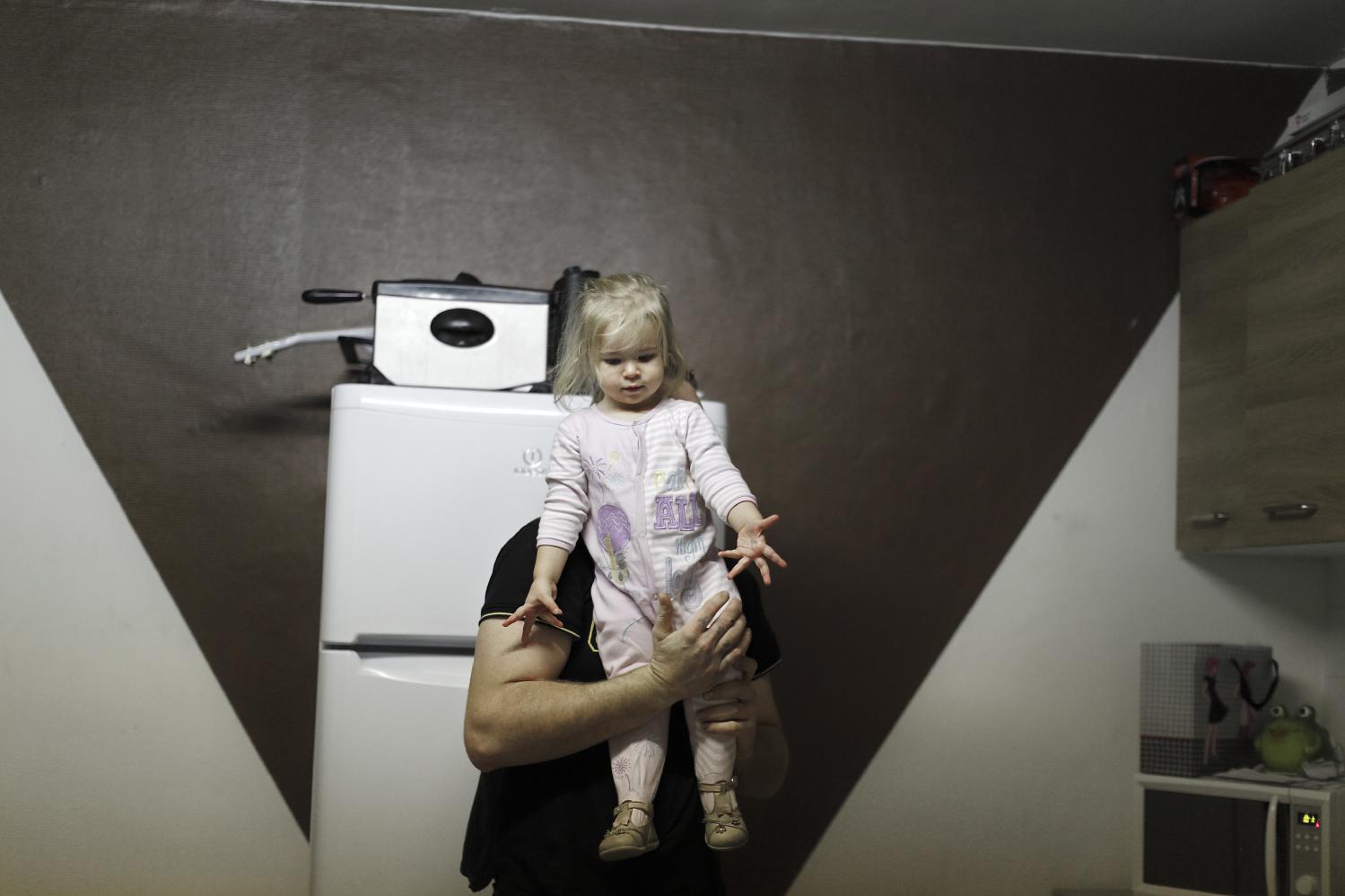 Leyna dans les bras de son père Steven. Bien qu'ils soient séparés, Steven voit régulièrement ses enfants. Fourmies, France.