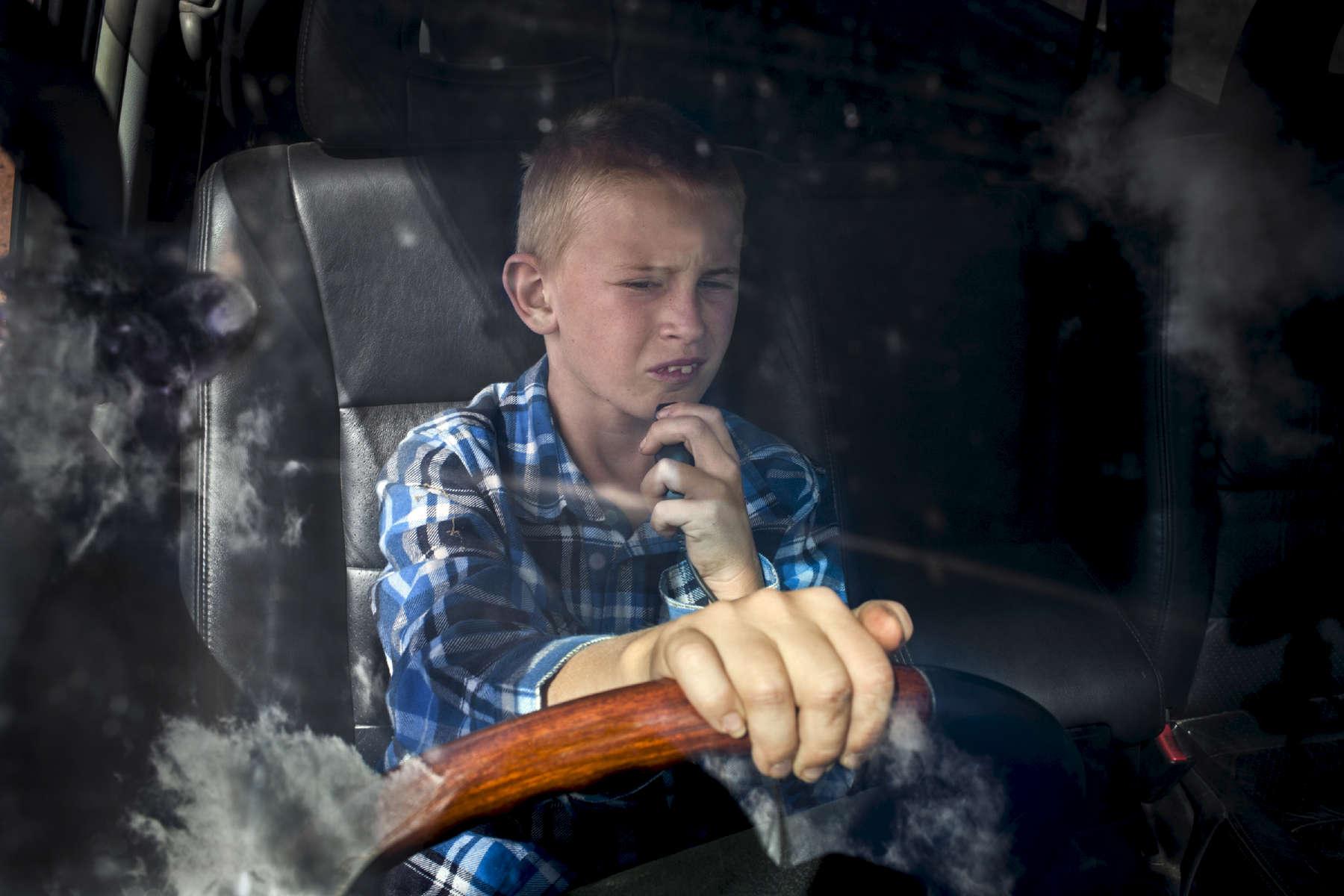 Henri, 11 ans au volant du 4x4 de ses parents, communique avec son père par radio. Il est commun dans l'Outback de voir les enfants conduire dès l'âge de 7 ans. Cela peut être utile tant pour le travail quotidien qu'en cas d'urgence. Ferme de Cawnalmurtee, Nouvelles Galle du Sud, Australie, 2011.