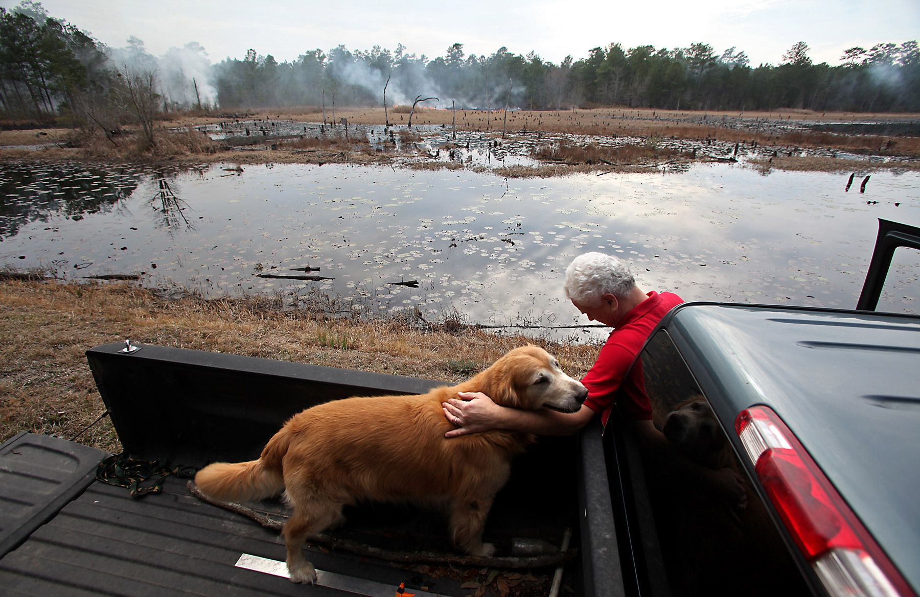 Medway Plantation property manager Bob Hortman and his dog Cooper, watch over a controlled burn at Medway Plantation, February 17, 2012 in Goose Creek, S.C. Hortman has lived and worked on the property for 34 years and oversees the day-to-day operations and maintenance of the plantation. Medway Plantation has 6728 total acres of land with 50 miles of maintained roads. In the South Carolina Lowcountry, more than a half-dozen antebellum plantations, which don't change hands often, are for sale.   REUTERS/Randall Hill