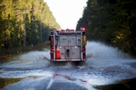 A firetruck speeds through flooded area along Dunbar Road in Georgetown, South Carolina October 8, 2015. Flooding from historic rainfall in South Carolina claimed two more lives on Wednesday, and the threat of further inundation from swollen rivers and vulnerable dams put already ravaged communities on edge.  REUTERS/Randall Hill