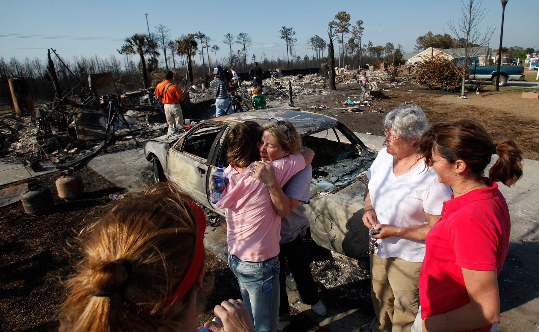 Neighbors and friends hug from left, Cindy Cumbo, her mother Jo Ann Portteus and Kathy Kuhn, during a break in the search for keep shakes Friday in front of the Portteus home in North Myrtle Beach. Bob and Jo Ann Portteus had the help of their three daughters and their families as residents living in the fire's affected areas were allowed back to their homes.