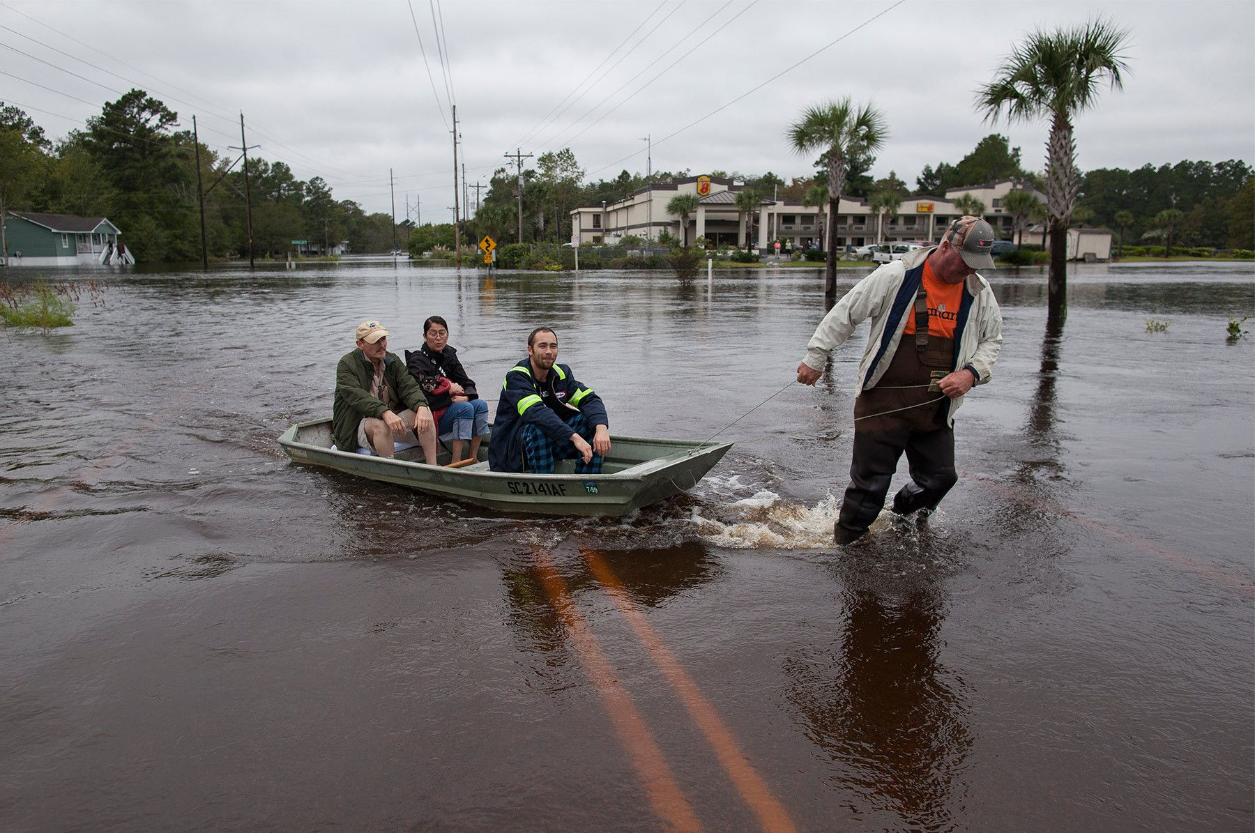 David Carroll (R) of Waccamaw Lake Drive, carries via boat, neighbors Rick Woodward, Miki Woodward and Matt Desjardins in Conway, South Carolina October 6, 2015. The Woodward family came to the landing from their flooded neighborhood to meet daughter Kelly who had been separated from them for a few days because of the floods. Floodwaters from unprecedented rainfall in South Carolina have killed 11 people, closed some 550 roads and bridges and prompted hundreds of rescues of people trapped in homes and cars, officials said on Monday. REUTERS/Randall Hill