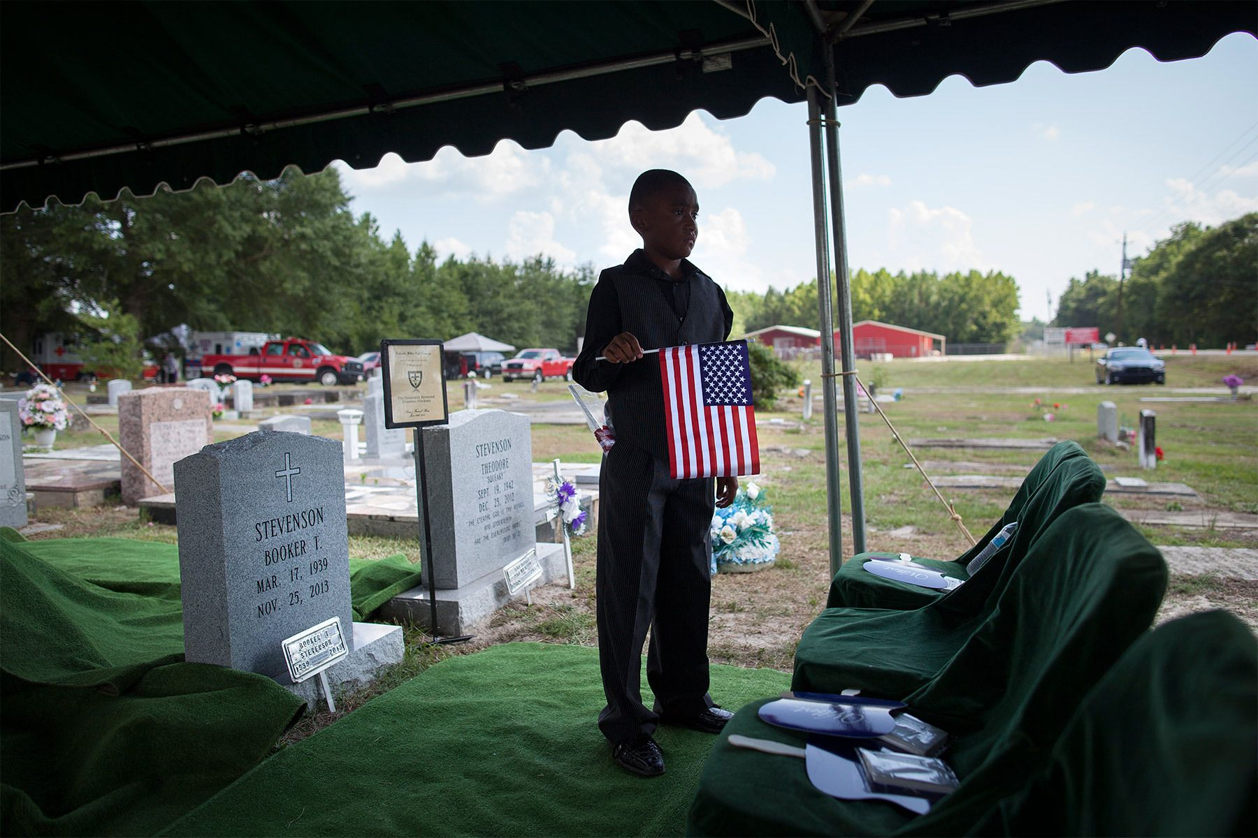 Family friend Kendrell Heriot (11) of Gresham, South Carolina, holds an American flag before the start of the burial service of Reverend Clementa Pinckney at the St James AME Church Cemetery in Marion, South Carolina June 26, 2015. Reverend Pinckney, a widely admired state senator and pastor of Charleston's Emanuel African Methodist Episcopal Church, was among the nine people who died when a gunman opened fire during Bible study.  REUTERS/Randall Hill