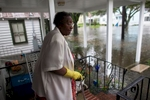 Ammie McKnight watches the level of flood waters in the front yard her Orange Street home in Georgetown, South Carolina October 4, 2015. Most major roads through the historical South Carolina city have closed due to flooding. Vast swaths of U.S. Southeast and mid-Atlantic states were grappling with heavy rains and flooding from a separate weather system which has already caused at least five deaths, washed out roads and prompted evacuations and flash flood warnings. REUTERS/Randall Hill