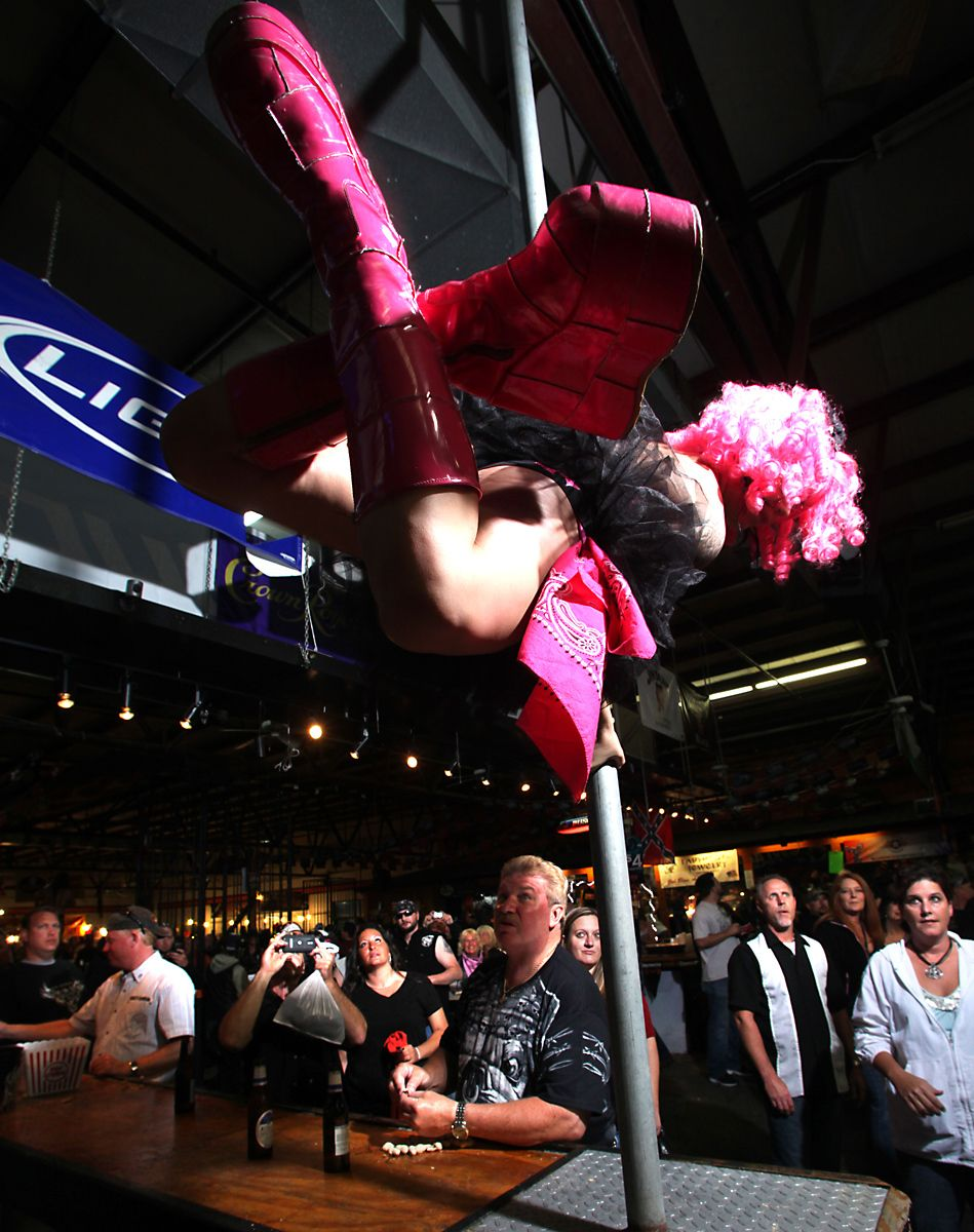 Anastashia Powell of the beer girl troupe Hell's Belles, performs on a dance pole at Suck Bang Blow biker bar, in Murrells Inlet, South Carolina, May 19, 2012.  The troupe of beer girls perform for tips during the annual Harley-Davidson Motorcycle Spring Rally in and around Myrtle Beach. Picture taken May 19, 2012.  REUTERS/Randall Hill