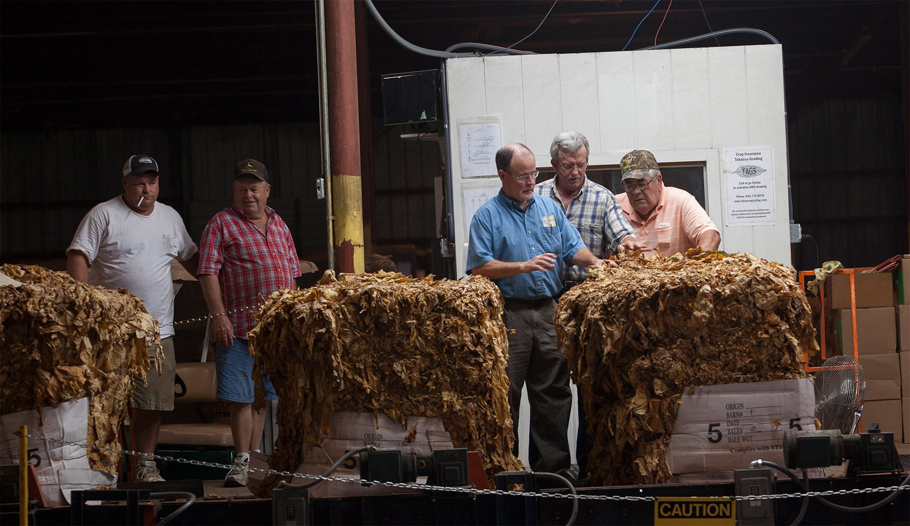 US Tobacco graders Jimmy Allen (third from left) and Scott Harrington, discuss a tobacco grade with warehouse manager Elton Johnson at the Big L Warehouse in Mullins, South Carolina July 29, 2013. The farm cooperative US Tobacco sets the standard for pricing and quality of the area farmer's crops at this warehouse. The traditional tobacco harvest requires many labor intensive hours to bring the crop to market, especially with the flue-cured variety prominent in the southern United States. With the growing health concerns with smoking in the US, most farmers use market cooperatives to sell their crop to the growing markets in China.      Picture taken on July 29, 2013.   REUTERS/Randall Hill (UNITED STATES)