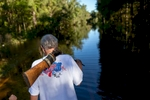 Harry Lockwood of River Road carries a rifle for snakes as he and his wife Kaye (Not Pictured) walk along flooded Lee's Landing Circle in Conway, South Carolina October 7, 2015. Rescuers searched early Wednesday for two people missing in floodwaters in South Carolina, while authorities urged residents in hundreds of homes to seek higher ground. REUTERS/Randall Hill
