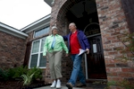 """Bob and Jo Ann Portteus walk out the front door of their recently completed Swift Street home on Wednesday evening en route for dinner plans with a neighbor. Their new home was built on the same property as their home destroyed during the April 2009 wildfires. """"Starting over was overwhelming,"""" said Jo Ann Portteus about the 6-months since the wildfires. """"Moving in was overwhelming. Then as we got the things that make this a home, it began to get better. Now its like we've been here all the time. It's over, it's past and we've moved on."""""""