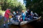 Scott Everett (L) helps his grandchildren enroute to school off a johnboat along Lee's Landing Circle in Conway, South Carolina October 7, 2015. The family has been living in their home surrounded by flood waters since Sunday evening. Scott Everett (L) helps his grandchildren enroute to school off a johnboat along Lee's Landing Circle in Conway, South Carolina October 7, 2015. The family has been living in their home surrounded by flood waters since Sunday evening. Rescuers searched early Wednesday for two people missing in floodwaters in South Carolina, while authorities urged residents in hundreds of homes to seek higher ground. REUTERS/Randall Hill