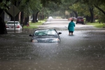 Clare Reigard of Georgetown, South Carolina, abandons her car after it stalled on Duke Street due to heavy rains in Georgetown, South Carolina October 4, 2015. Most major roads through the historical South Carolina city have closed due to flooding. Vast swaths of U.S. Southeast and mid-Atlantic states were grappling with heavy rains and flooding from a separate weather system which has already caused at least five deaths, washed out roads and prompted evacuations and flash flood warnings. REUTERS/Randall Hill