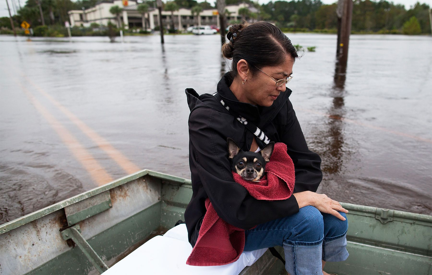 Miki Woodward holds family dog Butch while sitting on a johnboat along Waccamaw Drive in Conway, South Carolina October 6, 2015. The Woodward family came to the landing from their flooded neighborhood to meet daughter Kelly who had been separated from them for a few days because of the floods. Floodwaters from unprecedented rainfall in South Carolina have killed 11 people, closed some 550 roads and bridges and prompted hundreds of rescues of people trapped in homes and cars, officials said on Monday. REUTERS/Randall Hill