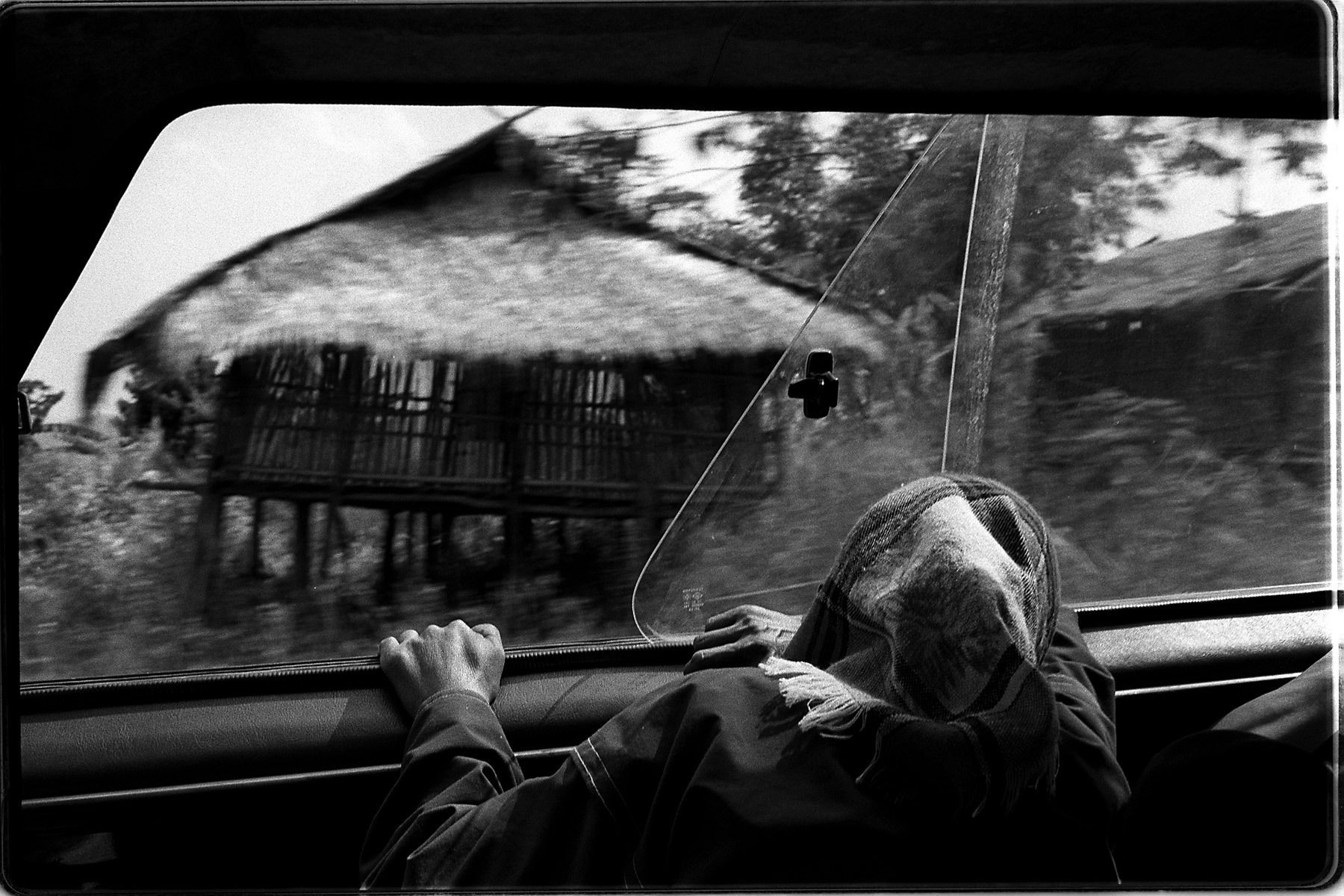 Tucked in Thailand's northern border, Maesalong is a place of contrasts. It's a freedom mecca from it's oppressive neighbors in China, Laos and Burma. Caught between are the Akha tribal people who have been forced from their nomadic tradition because of politics and strict borders. This photo: Ahbu travels in the back of a truck from her home in Maesalong, Thailand to Chiang Rei to receive treatments for her opium addiction. Having ridden in an automobile only once in her life, the hour-long journey has made her sick.