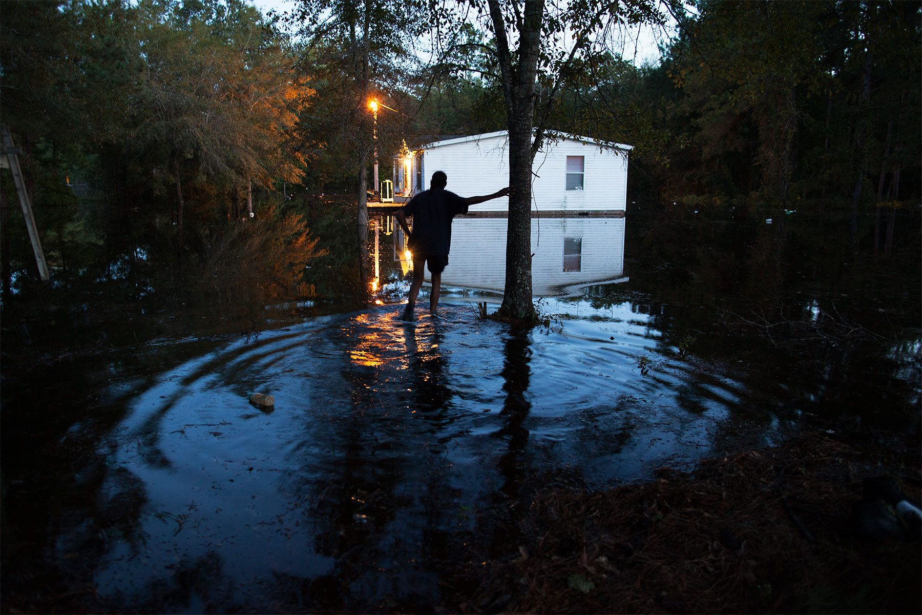 Lewis Johnson makes his way to help a neighbor remove valuables from a flooded home on Frank Williams Road in Georgetown, South Carolina October 8, 2015. South Carolina's governor warned on Thursday that several coastal areas were about to be hit by a second round of major flooding, while residents inland hauled soaked furniture and appliances from homes left in ruins by unprecedented rainfall.  REUTERS/Randall Hill