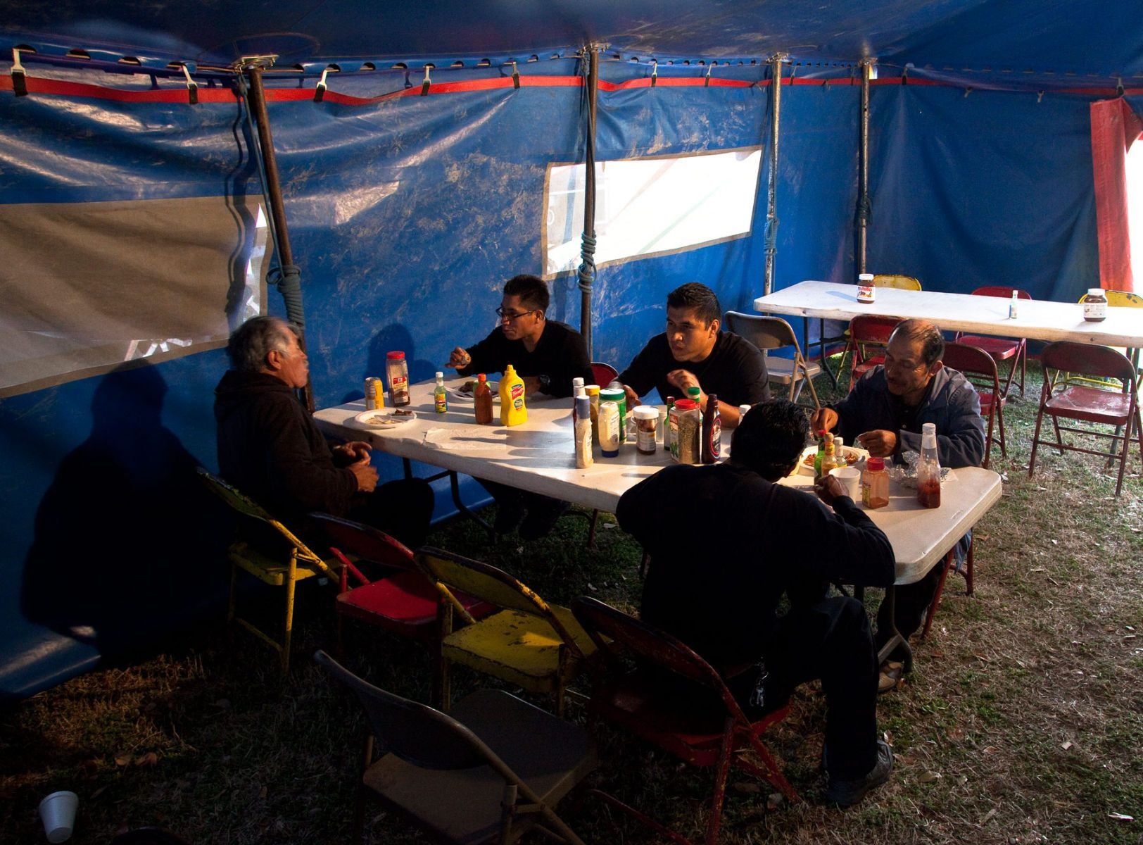 Tent crews grab a bite to eat in the mess tent at Cole Brothers Circus of the Stars during its stop in Myrtle Beach, South Carolina March 31, 2013. The circus prepares 3 meals a day for the 70 workers that travel with the circus. Traveling circuses such as the Cole Brothers Circus of the Stars, complete with it's traveling big top tent, set up their tent city in smaller markets all along the East Coast of the United States as they aim to bring the circus to rural areas. The Cole Brothers Circus, now in its 129th edition, travels to 100 cities in 20-25 states and stages 250 shows a year.  REUTERS/Randall Hill   (UNITED STATES)