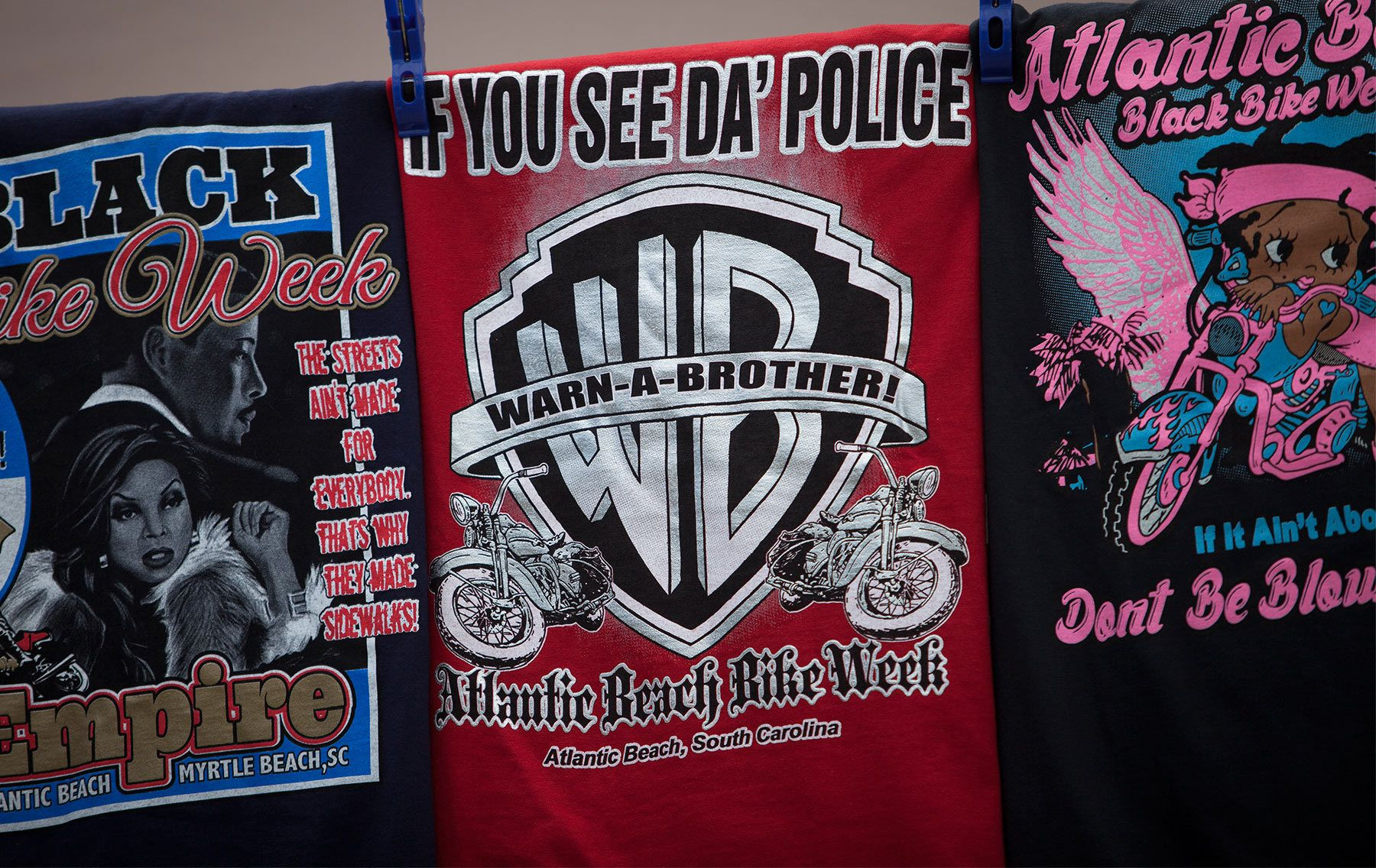 T-shirts are for sale at a vendor's booth during the 2015 Atlantic Beach Memorial Day BikeFest in Atlantic Beach, South Carolina May 22, 2015. After three people were killed and seven wounded in shootings during 2014 Bikefest, State officials called for an end to the event that draws thousands to the family-friendly beach town.Their efforts were unsuccessful. Bikers returned to Myrtle Beach - just a week after a bloody motorcycle gang shootout in Waco, Texas. But this time authorities are more prepared, with dozens of new surveillance cameras and a police force three times the size of last year's.    REUTERS/Randall Hill