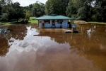 A community store in the Dunbar Community is surrounded by water in Georgetown, South Carolina October 9, 2015. Concerns about additional inundation in four coastal counties and more rain had officials on guard Friday, nine days after a state of emergency was declared because of historic rains that washed out roads, swamped hundreds of homes and killed 17 people in the state. Emergency management officials in several areas were encouraging residents to leave their homes as a precaution as floodwaters flow south into already-swollen rivers and tributaries toward the Atlantic Ocean.  REUTERS/Randall Hill