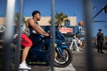 A biker is seen through the metal fencing blocking both sides of Ocean Boulevard during the 2015 Atlantic Beach Memorial Day BikeFest in Myrtle Beach, South Carolina May 24, 2015. After three people were killed and seven wounded in shootings during 2014 Bikefest, State officials called for an end to the event that draws thousands to the family-friendly beach town. Their efforts were unsuccessful. Bikers returned to Myrtle Beach - just a week after a bloody motorcycle gang shootout in Waco, Texas. But this time authorities are more prepared, with dozens of new surveillance cameras and a police force three times the size of last year's. REUTERS/Randall Hill