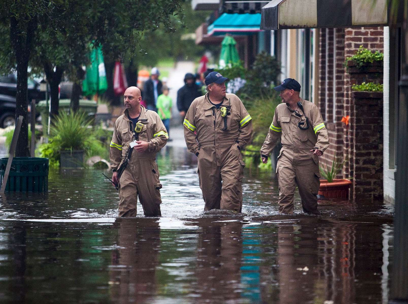 Norman Beauregard, (From Left) Kevin Attender and Chris Rogers, all with the Georgetown Fire Department, wade through flooded Front Street in Georgetown, South Carolina October 4, 2015. Most major roads through the historical South Carolina city have closed due to flooding. Vast swaths of U.S. Southeast and mid-Atlantic states were grappling with heavy rains and flooding from a separate weather system which has already caused at least five deaths, washed out roads and prompted evacuations and flash flood warnings. REUTERS/Randall Hill