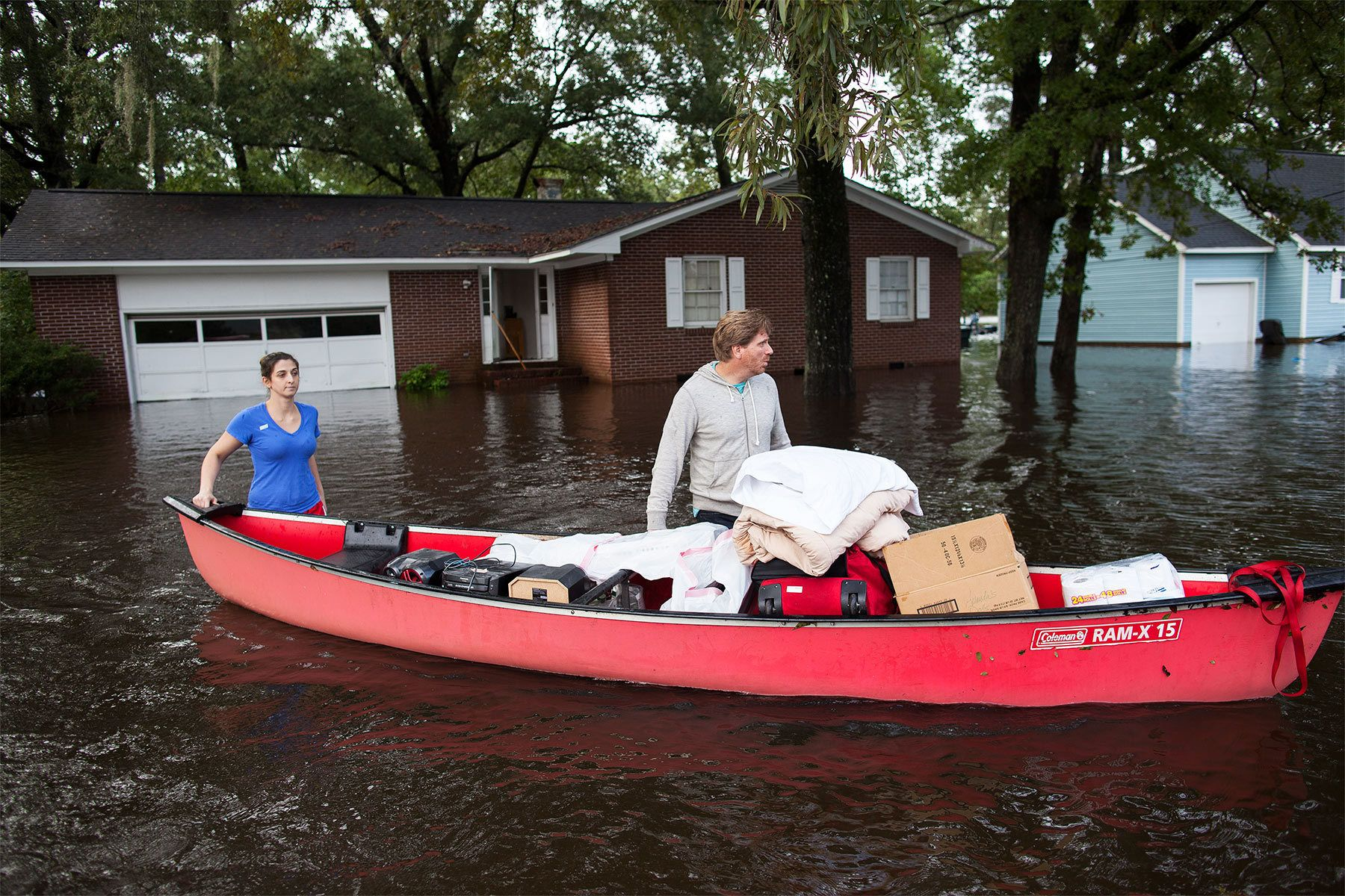 Greg Rodermond (R) and Mandy Barnhill, use a canoe to evacuate Mandy's home on Long Avenue in Conway, South Carolina October 5, 2015. Torrential rainfall that South Carolina's governor called a once-in-a-millennium downpour triggered flooding in the southeastern U.S. state on Sunday, causing at least eight deaths in the Carolinas. The storm had dumped more than 20 inches (50 cm) of rain in parts of central South Carolina since Friday, the National Weather Service said. The state climatologist forecast another 2 to 6 inches (5 to 15 cm) through Monday as the rain began to slacken. REUTERS/Randall Hill