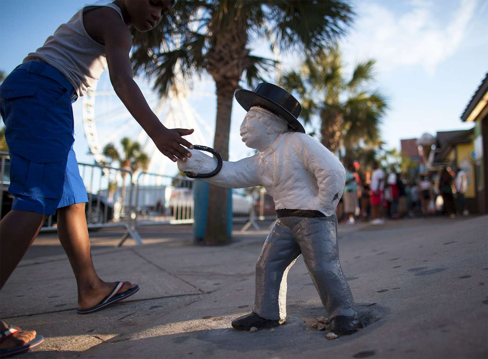 A boy touches an old racial lawn jockey that has been painted white on Ocean Boulevard during the 2015 Atlantic Beach Memorial Day BikeFest in Myrtle Beach, South Carolina May 24, 2015. After three people were killed and seven wounded in shootings during 2014 Bikefest, State officials called for an end to the event that draws thousands to the family-friendly beach town. Their efforts were unsuccessful. Bikers returned to Myrtle Beach - just a week after a bloody motorcycle gang shootout in Waco, Texas. But this time authorities are more prepared, with dozens of new surveillance cameras and a police force three times the size of last year's. REUTERS/Randall Hill