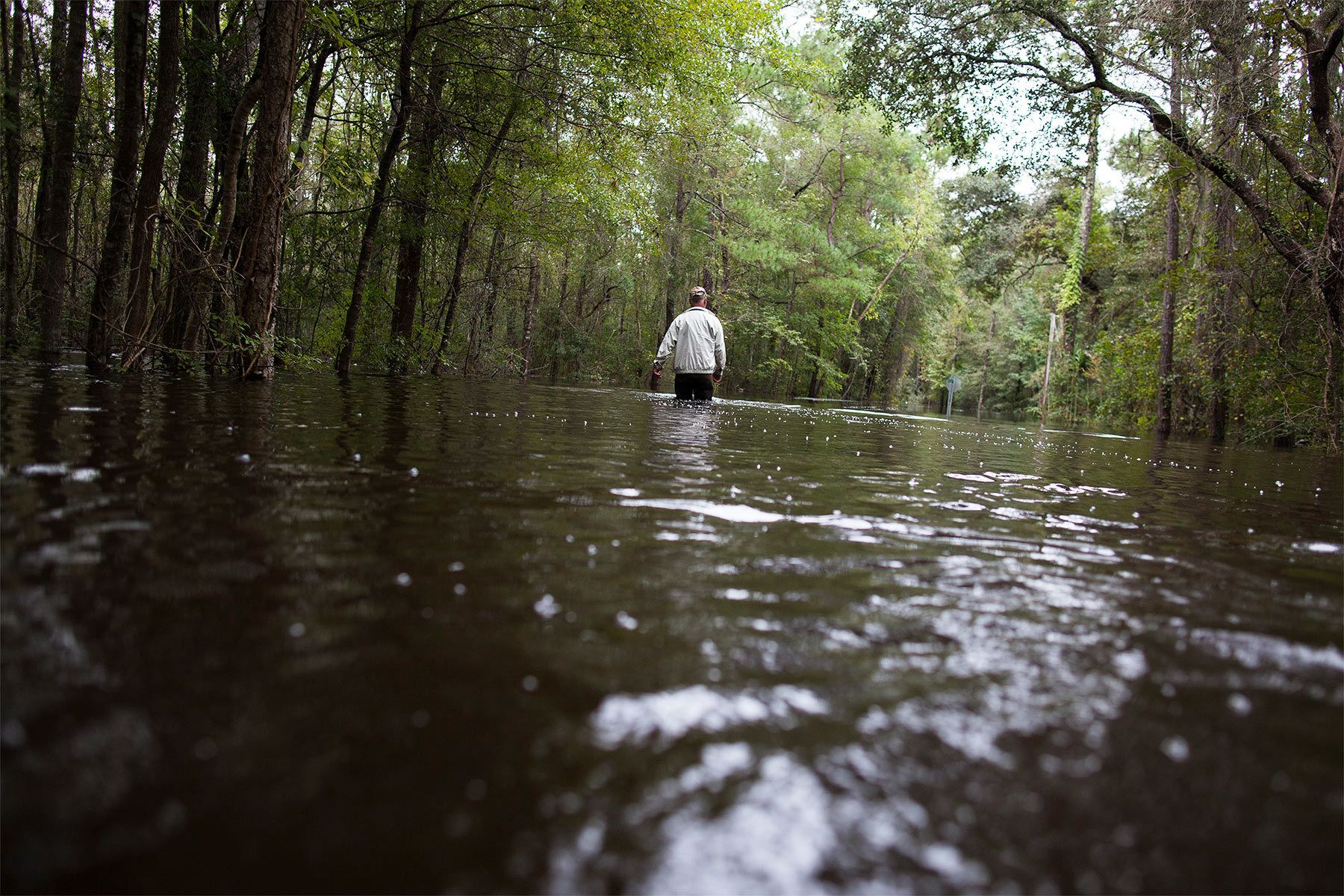David Carroll of Waccamaw Lake Drive, walks down his flood covered road to meet family in Conway, South Carolina October 6, 2015. Carroll has been living with several feet of water around his home since Saturday. Floodwaters from unprecedented rainfall in South Carolina have killed 11 people, closed some 550 roads and bridges and prompted hundreds of rescues of people trapped in homes and cars, officials said on Monday. REUTERS/Randall Hill